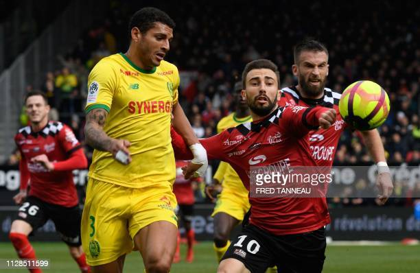 Guingamp's French forward Nicolas Benezet vies for the ball with Nantes' Brazilian defender Diego Carlos during the French L1 football match between...