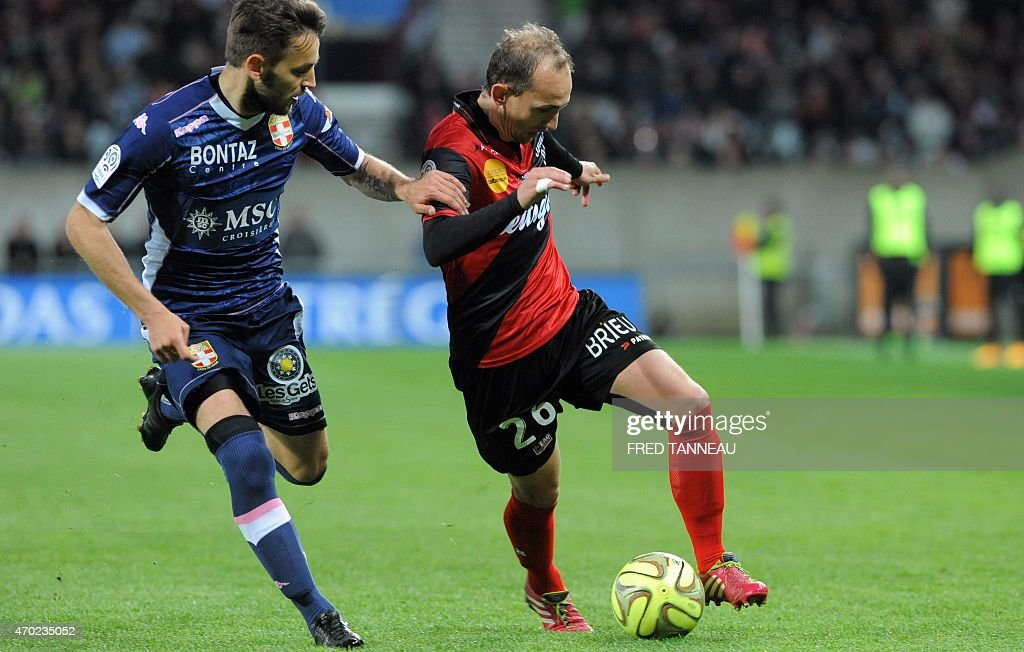 Guingamp's French forward Thibault Giresse (R) vies with Evian's midfielder Milos Ninkovic during the French L1 football match between Guingamp and Evian on April 18, 2015 at the Roudourou stadium in Guingamp, western of France.