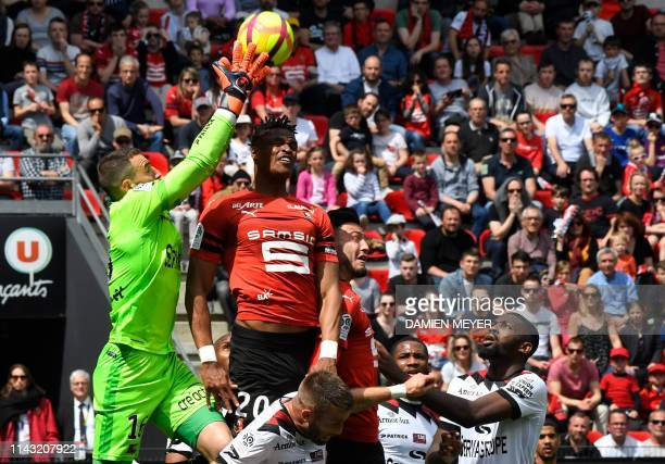 TOPSHOT Guingamp's French goalkeeper MarcAurele Caillard jumps to catch the ball next to Rennes' French defender Gerzino Nyamsi during the French...