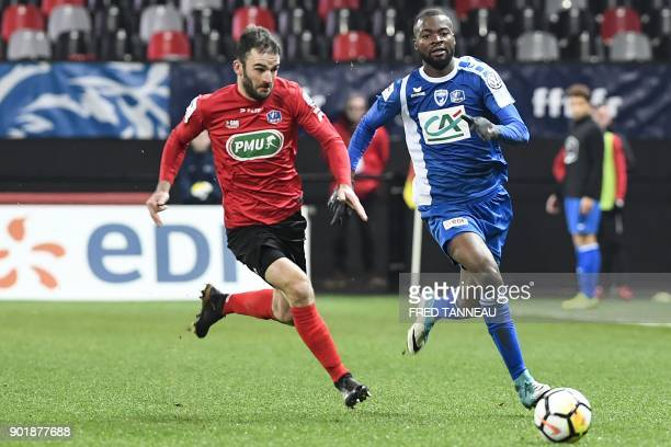 Guingamp's French midfielder Christophe Kerbrat vies with Niort's Cameroonian forward Didier Lamkel Ze during the French Cup football match between...