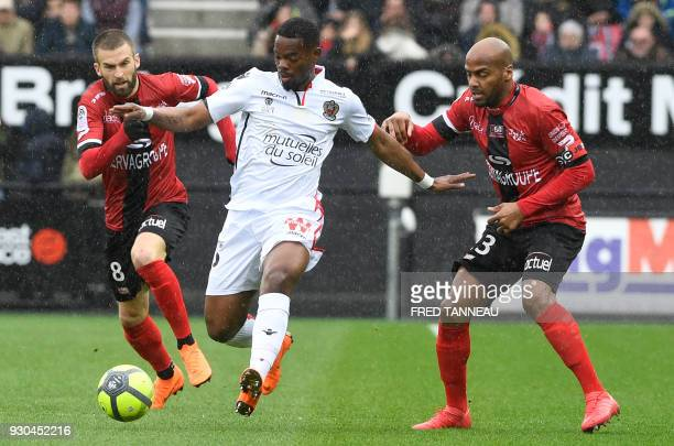 Guingamp's French midfielder Lucas Deaux and Guingamp's French forward Jimmy Briand vie for the ball against Nice's French midfielder Wylan Cyprien...