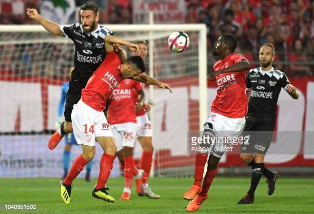 Guingamp's French midfielder Lucas Deaux vies with Nimes' French midfielder Antonin Bobichon and Nimes' French mifielder Moustapha Diallo during the...