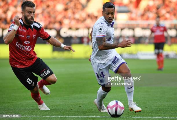 Guingamp's French midfielder Lucas Deaux vies with Toulouse's Togolese midfielder Mathieu Dossevi during the French L1 football match between...