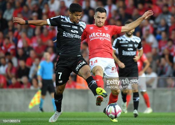 Guingamp's French midfielder Ludovic Blas vies with Nimes' French midfielder Antonin Bobichon during the French L1 football match between Nîmes and...