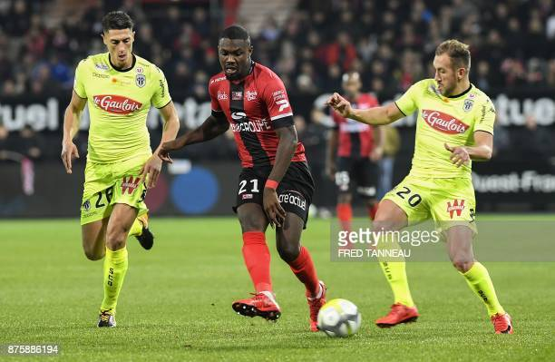 Guingamp's French midfielder Marcus Thuram vies with Angers's Algerian defender Mehdi Tahrat and Angers' French midfielder Flavien Tait during the...