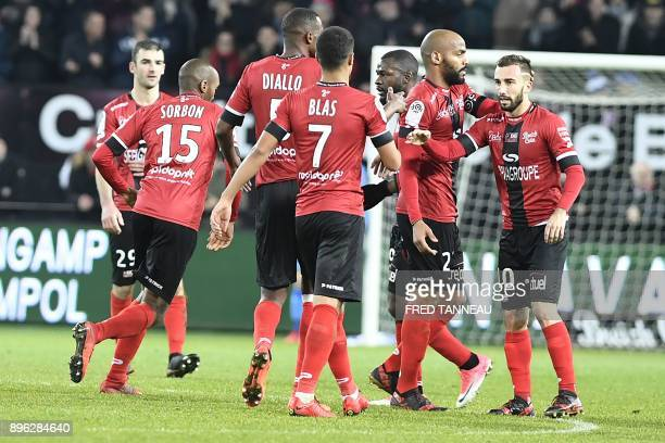 Guingamp's French midfielder Nicolas Benezet is congratulated by his teammates after scoring during the French L1 football match Guingamp against...