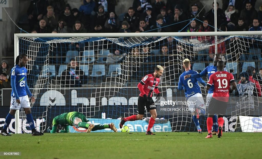 Guingamp's French midfielder Nicolas Benezet (C) scores during the French L1 football match between Strasbourg (RCSA) and Guingamp (EAG) on January 12, 2018 at the Meinau stadium in Strasbourg, eastern France. /