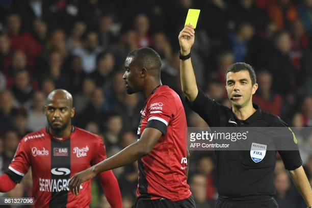 Guingamp's Senegalese midfielder Moustapha Diallo receives a yellow card by French referee Frank Schneider during the French Ligue 1 football match...