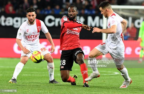 Guingamp's South African midfielder Lebogang Phiri fights for the ball with Nîmes' French midfielder Jordan Ferri and Nîmes' French midfielder...