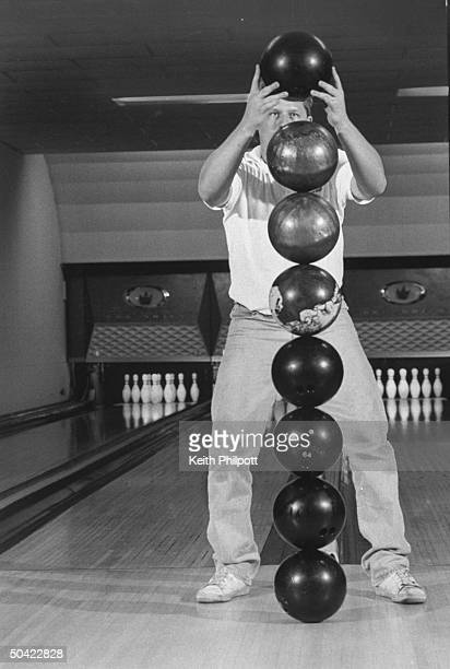 Guinness Book of World Records contender Dave Kremer standing behind stack of eight bowling balls he balances at his local bowling alley