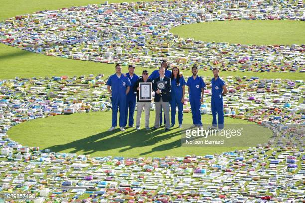Guinness World Records Adjudicator Philip Robertson presents the 99 Cents Only Stores team with the Largest packaged product number title at the Rose...