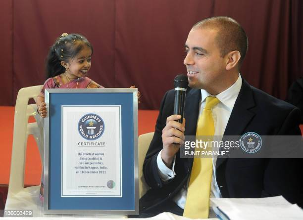 Guinness World Records Adjudicator Rob Molloy speaks with Jyoti Amge as he holds an official certificate from Guinness World Records in Nagpur on...