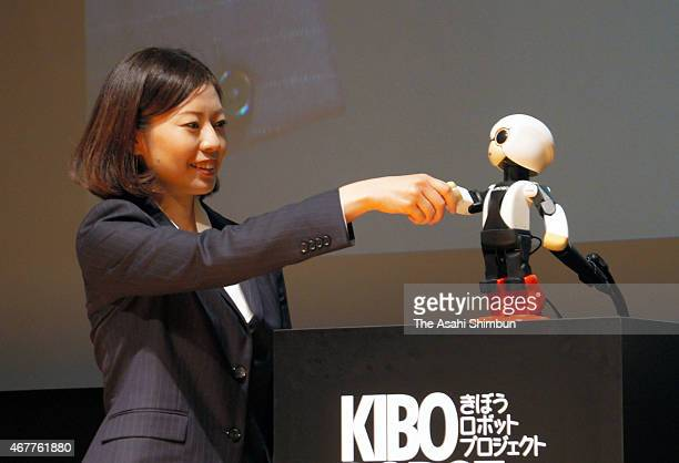 Guinness World Records Japan vice president Erika Ogawa shakes hands with humanoid robot 'Kirobo' during the award ceremony on March 27 2015 in Tokyo...