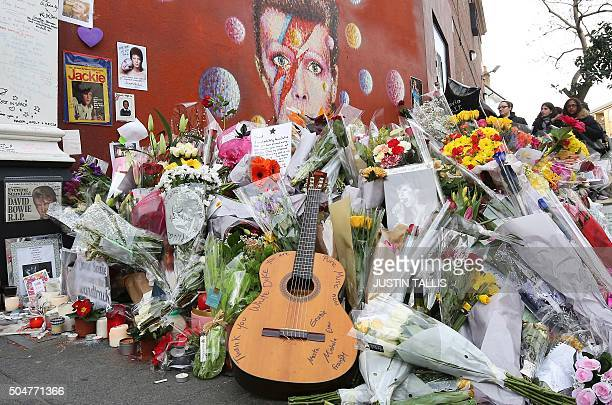 A guitar and floral tributes are piled in front of a mural of British singer David Bowie painted by Australian street artist James Cochran aka Jimmy...