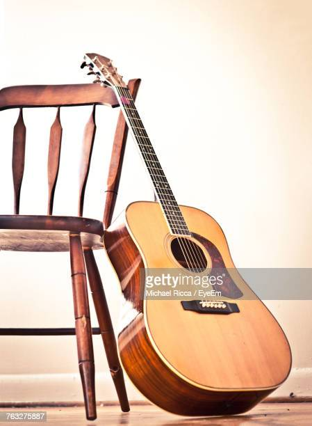 Guitar By Wooden Table On Floor