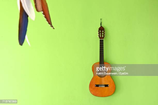 guitar hanging on green wall - classical guitar stock photos and pictures
