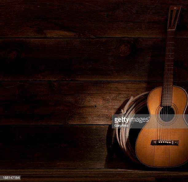 A guitar in the shadows, leaning against the wall