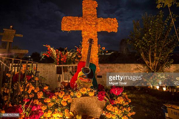 A guitar is part of the grave decoration during the celebration of the Day of the Dead in which people remember those relatives and friends that have...