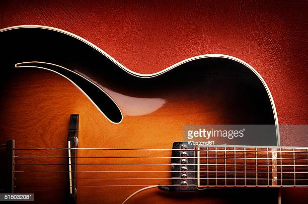 guitar leaning against red wall - chitarra foto e immagini stock