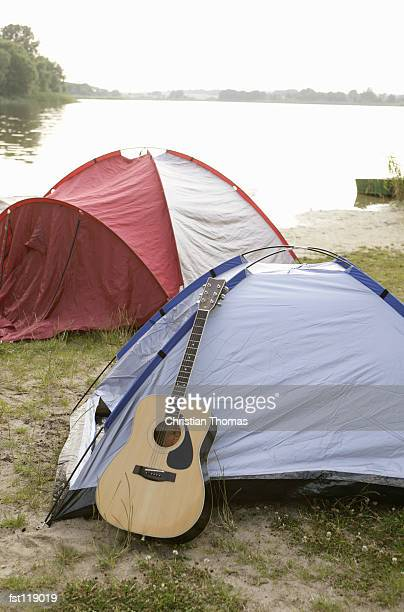 guitar leaning on tent - small group of objects stock pictures, royalty-free photos & images