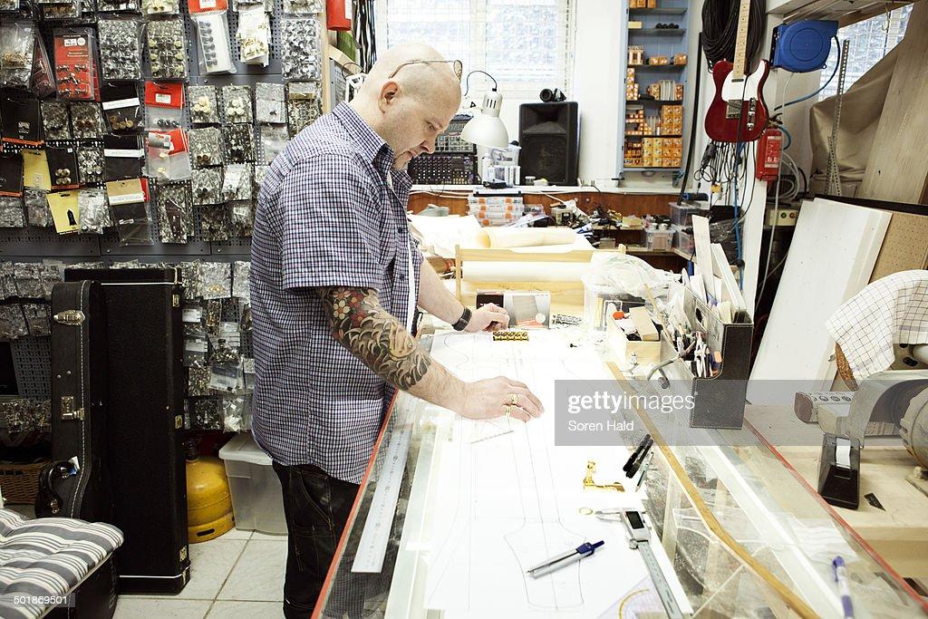 Guitar maker measuring up blueprint design on drawing table stock guitar maker measuring up blueprint design on drawing table stock photo malvernweather Images