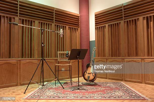 Guitar, music sheet and microphone in recording studio