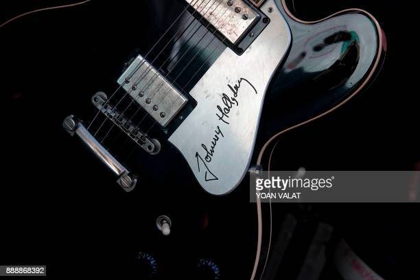 A guitar of late French singer Johnny Hallyday is on display by the Madeleine church during his funeral ceremony on December 9 2017 in Paris French...