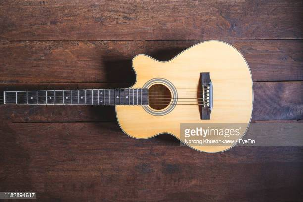guitar on hardwood floor - acoustic guitar stock pictures, royalty-free photos & images