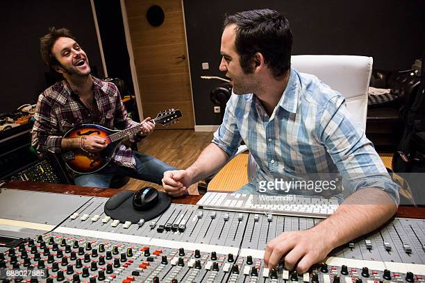 Guitar player and audio engineer in a recording studio