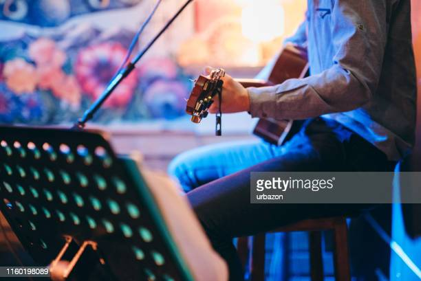 guitar player in a café - arts culture and entertainment stock pictures, royalty-free photos & images