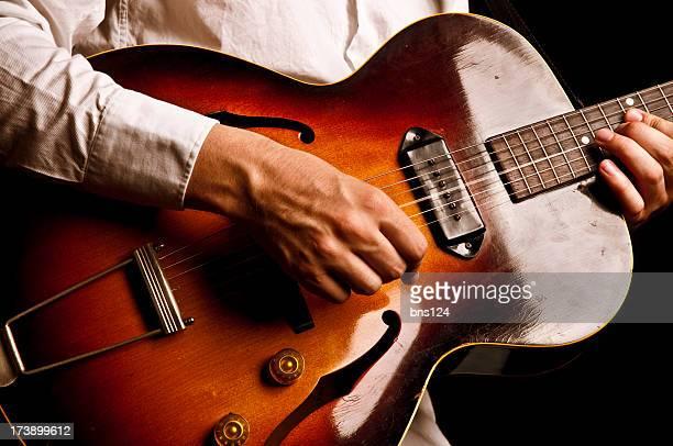 Gitarrenspieler, auf schwarzem Hintergrund