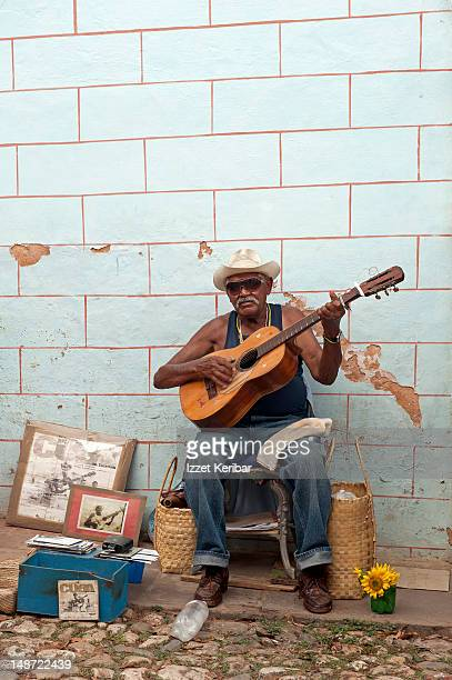 Guitar player sitting in front of wall, selling old pictures and CDs.