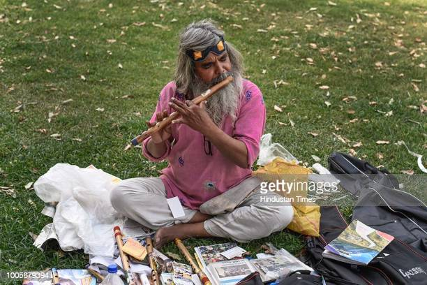 Guitar Rao plays flute in the lawns at Vijay Chowk, where he daily spends 4 hours teaching music to passersby and some music enthusiast staff of...