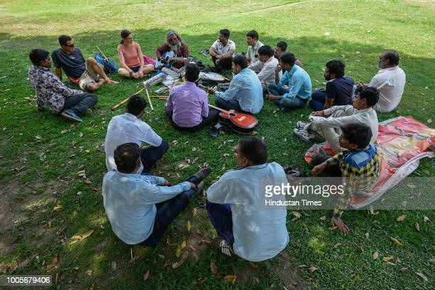 Guitar Rao plays guitar in the lawns at Vijay Chowk, as people crowd around him on May 22, 2018 in New Delhi, India. His lessons dont require a...