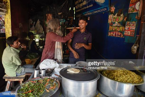 Guitar Rao tries to teach a quick class of flute to a roadside food vendor on May 22, 2018 in New Delhi, India. A former civil engineer, Rao today...