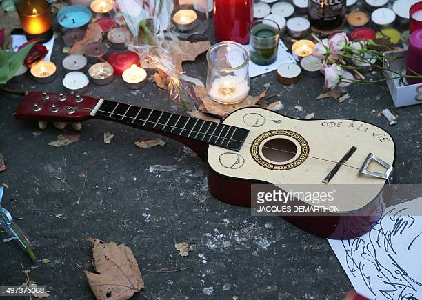 A guitar reading 'Ode to life' is placed at a makeshift memorial in tribute to the victims of the Paris attacks on November 15 2015 at the La Belle...