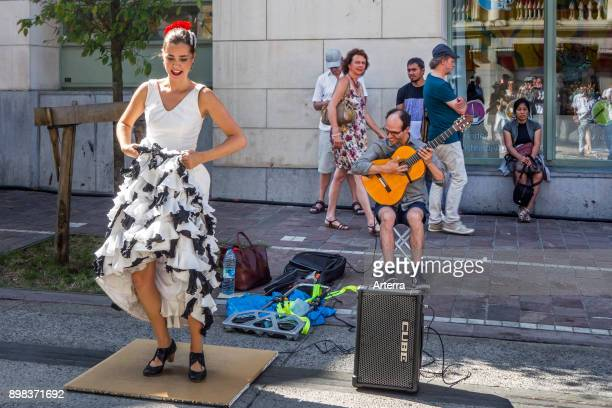 Guitarist and flamenco dancer with traditional white dress dancing as street performance during summer festivities