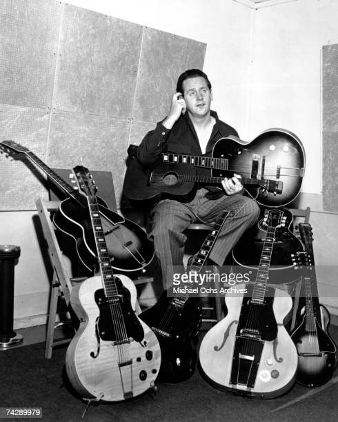 Guitarist and inventor Les Paul poses with his inventions for a portrait in his garage studio on in 1946