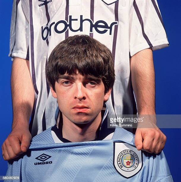 Guitarist and songwriter Noel Gallagher of British rock group Oasis in a Manchester City shirt Portsmouth 9th May 1994 Standing behind him is his...