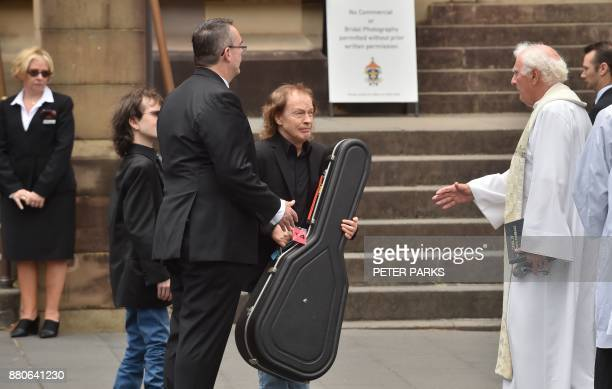 AC/DC guitarist Angus Young carries a guitar case after the funeral service for his brother AC/DC cofounder Malcolm Young outside St Mary's Cathedral...