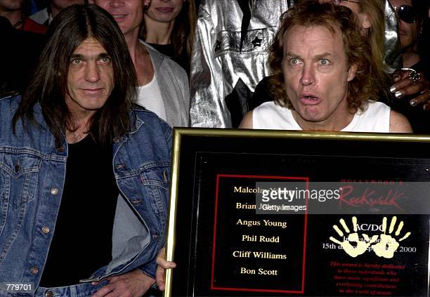 Guitarist Angus Young of the Australian rock band ACDC right holds plaque as brother and bandmate Malcolm Young looks on after the Rock Walk...