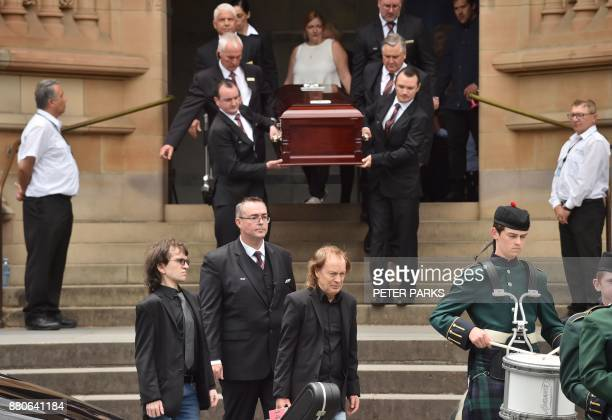 AC/DC guitarist Angus Young walks ahead of the coffin of his brother AC/DC cofounder Malcolm Young as they leave St Mary's Cathedral following his...