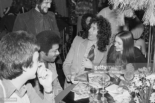 Guitarist Brian May of British rock band Queen receives a copy of 'Astounding Science Fiction' during a party thrown by Elektra Records 1977 The...
