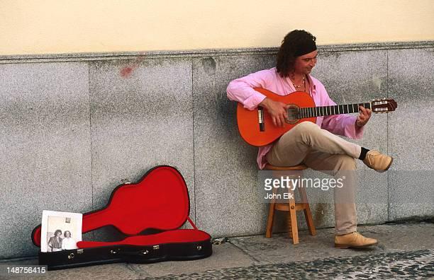 Guitarist busking in street.