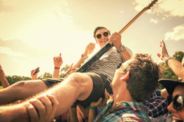 Rock star crowd surfing at rock concert
