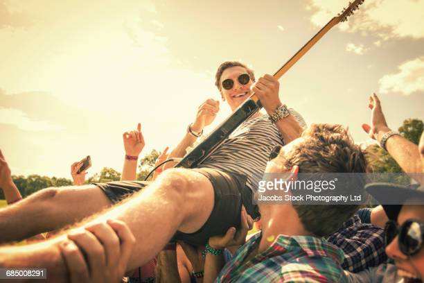 Guitarist crowd surfing at concert