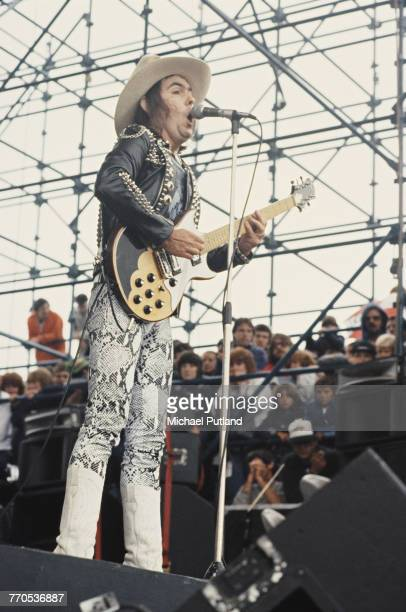 Guitarist Dave Hill wearing snakeskin trousers performs with British rock group Slade at the Monsters of Rock festival at Donington Park...