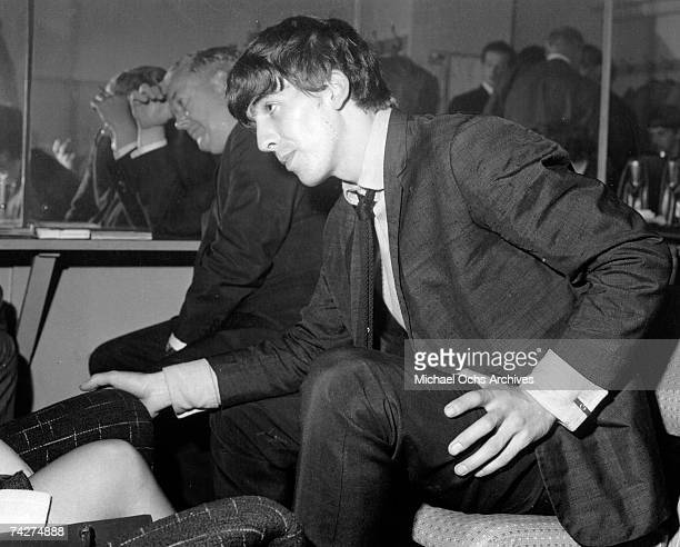 Guitarist George Harrison of the rock and roll band 'The Beatles' leans in to speak with someone in 1964