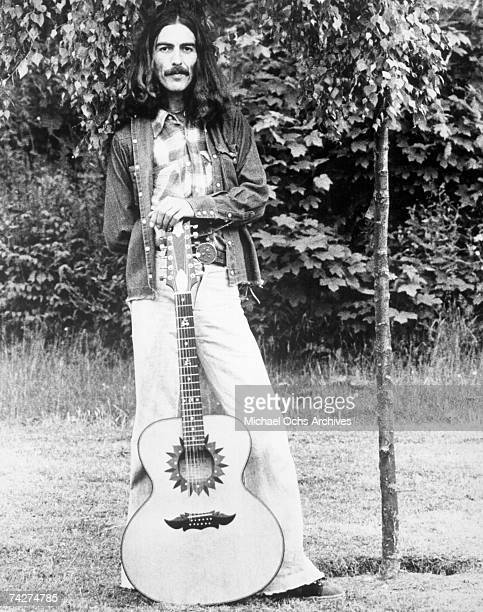 Guitarist George Harrison poses for a portrait with an acoustic guitar in circa 1974