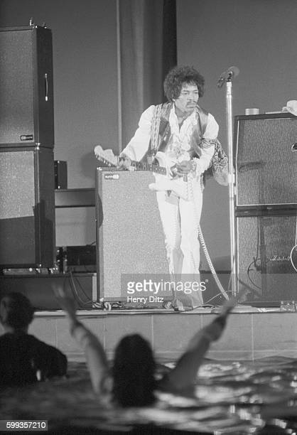 Guitarist Jimi Hendrix playing at Hollywood bowl in 1968 Some fans have jumped into the pond and are waving their arms
